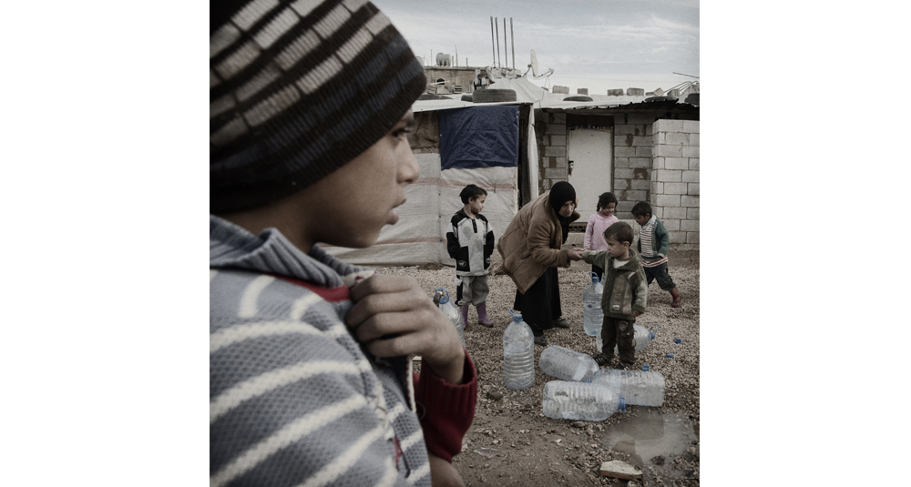Luca Sola, Lebanon, Bekaa Valley, January 18, 2013.  In a large number of informal settlement, during the first winter after the beginning of the so called Syrian Revolution, refugees have access to the water just one hour a day, when the sun melts the ice in the water pipes. Courtesy All Around Art, Milan