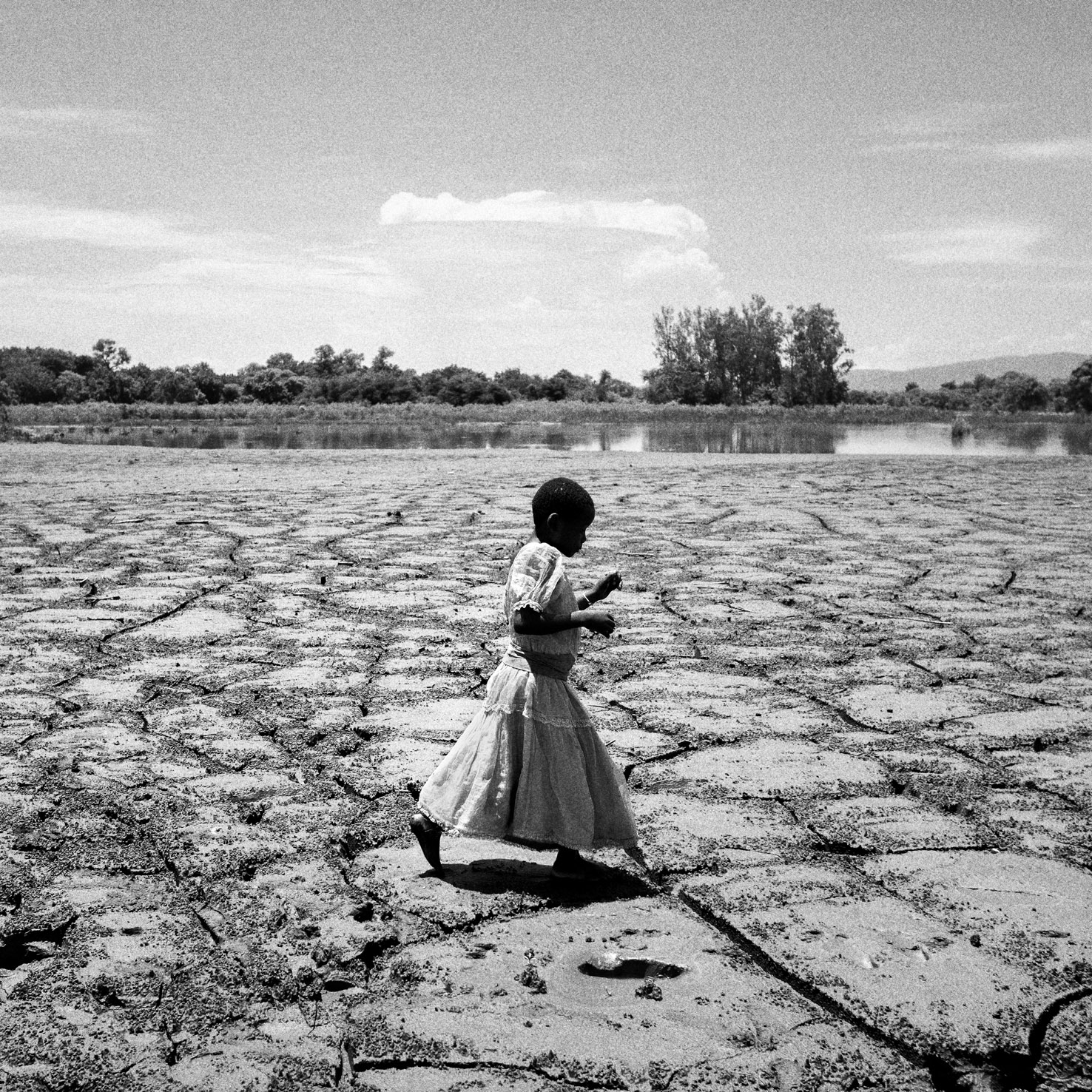 MALAWI. Nsanje District. Makhanga. February 03, 2015. Alesi Phiri, 7yo, walks on a former crop field as she looks to the thick coat of dried mud.  © Luca Sola 2015