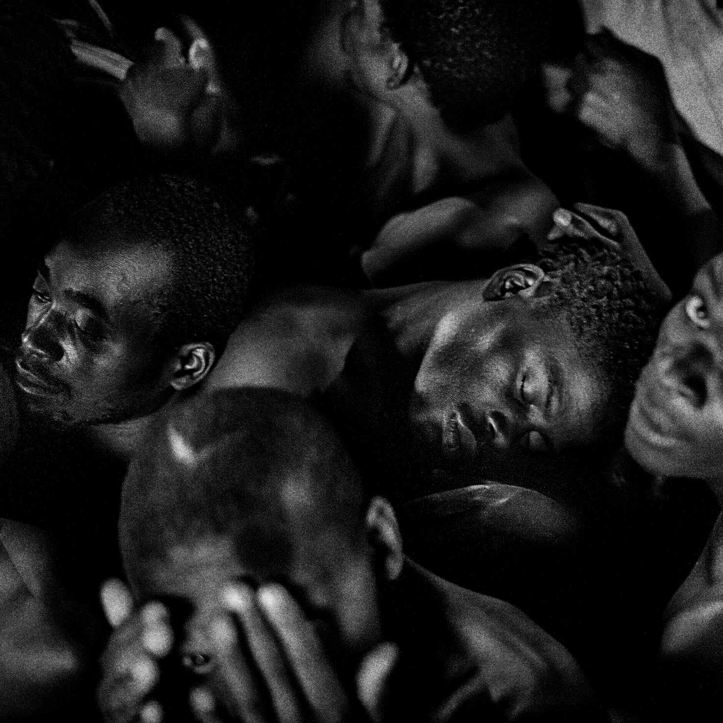 MALAWI. Blantyre. May 26th, 2015. Chichiri Prison. Prisoners sit in an overcrowded cell (cell 5) during the night, struggling to find some sleep.  Overcrowding represent the most critical problem of Malawian jails. Chichiri Prison was built to house 800 prisoners instead of the 1800 currently detained in.    According to medical statistics the cell 5, one of the most overcrowded, is the cell in which there are more case of viral transmissions (Tuberculosis, Hepatitis, Malaria, HIV) as well as the highest percentage of other diseases related to the critical hygienically conditions (Scabies, skin infections, rash).  © Luca Sola 2015