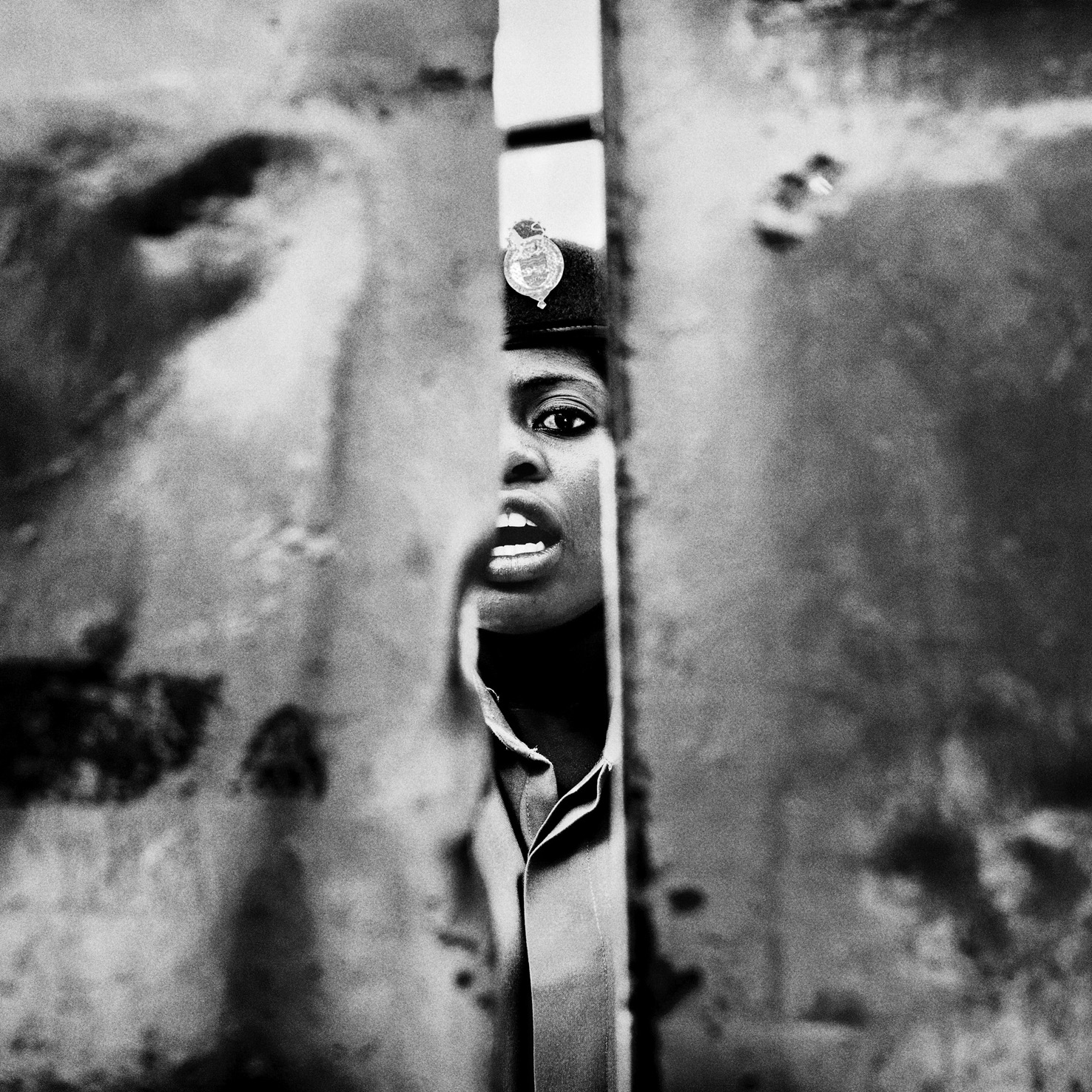 MALAWI. Blantyre. May 27th, 2015. Chichiri Prison. A prison guard closes the prison's main gate as she shouts to detained's relatives [not pictured] that the parental visit time is over.  © Luca Sola 2015